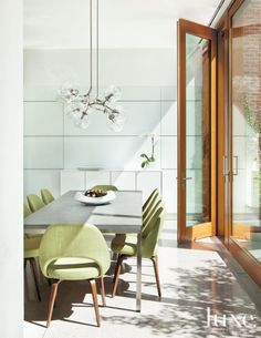 Modern White Breakfast Area with Green Chairs -- Green is carried through to the breakfast area in linen from Cowtan & Tout on a set of reproduction Saarinen Executive chairs from Knoll. The light fixture is from Lindsey Adelman Studio in New York.