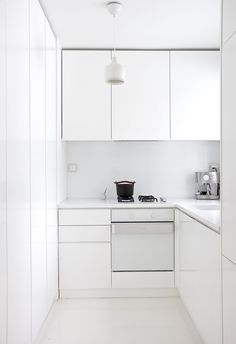Pure white kitchen. Handle-less units. White recon worktop