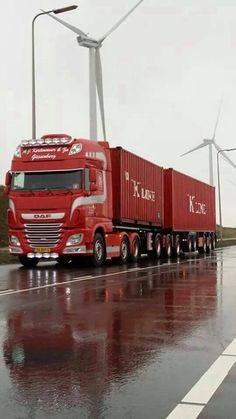 DAF articulated lorry carrying intermodal containers. Wind turbines in the background.