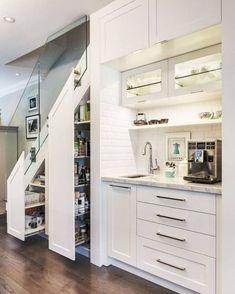 A ideia de dar utilidade ao espaço embaixo da escada desta casa, em Toronto, no Canadá, foi da designer de interiores Lisa Robazza. No nível mais baixo, armários de correr verticais foram instalados e funcionam como uma despensa. À direita, subway tiles e uma bancada compõem o espaço dedicado ao café, que inclui pia, gavetas e mais armários. Foto Dave Remple #revistacasaclaudia #decor #decoration #decoração #home #house #casa #homedecor