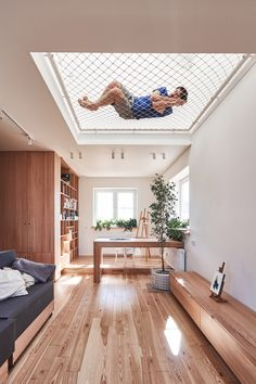 Russian architecture studio Ruetemple has renovated a family home in Moscow, creating an open living space using suspended nets for children to play in.