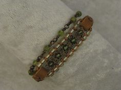 This sweet little double wrap bracelet is 15 1/4 inches long by 1/2 inch wide, perfect for a 7 1/4 inch wrist. I used round Peridot beads, 2 types of copper flowers, peridot colored glass beads,...@ artfire