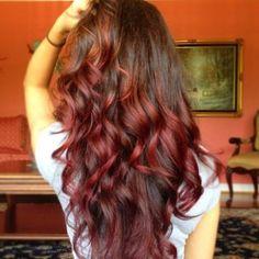 Pour mettre en évidence les boucles qui ont été dessinées dans les longs cheveux dégradés de cette femme, le coiffeur a choisi de leur donner une teinte rougeâtre. Les longues racines, quant à elles, sont brunes. Le contraste n'est donc pas trop prononcé entre les teintes.