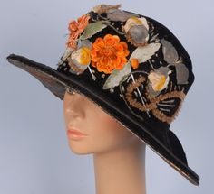 LADY'S WIDE BRIM CLOCHE, 1910-1920. Black velvet having oval brim, crown appliqued with cloth flowers, under-brim having printed lame in a Deco pattern.
