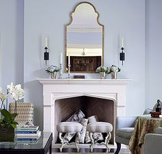 Cool, crisp, light blue fireplace vignette by Suzanne Kasler reads almost Scandinavian in its clean simplicity. Love the gothic arch of the limestone fireplace, the slim lines of the mirror above, the dark petite sconces, and the hydrangeas on silver julep cups.