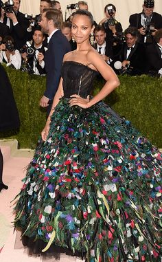 2016 Met Gala: Zoe Saldana makes a grand entrance in a multi colored feathered D&G gown with a long train and a black semi sheer bodice. Way to make a statement! This is a gorgeous gown and the perfect event to wear it to!