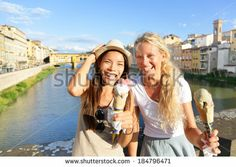 Happy women friends eating ice cream on travel in Florence. Cheerful girlfriends enjoying italian food gelato cone smiling happy by Ponte Vecchio during vacation holidays in Tuscany, Italy, Europe. - stock photo
