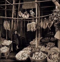 Seated Man Amid Baskets Of Fish & Hanging Dried Fish, Eastern Districts, Hong Kong Island [c1946]