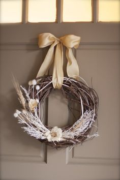 wreath... love the bow to hang it and the brown wreath with white accents...