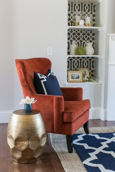 This glamorous stool end table is a gorgeous accent in this contemporary living room. It plays off of the burnt orange armchair and navy blue rug perfectly!