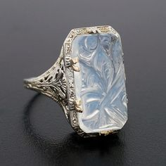 A fabulous moonstone ring from the Art Deco! Simply stunning, the ring is made of 18kt white gold and displays a large (5/8 x 3/8 x 1/8) rectangular-shaped moonstone center. The moonstone, which is prong set within a stunning filigree mounting, is hand carved and carries a feminine floral motif.