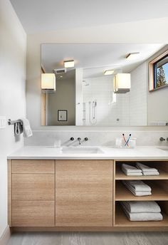 15 Examples Of Bathroom Vanities That Have Open Shelving // The combination of drawers, a cabinet, and open shelving, make for a variety of bathroom storage options in this wooden vanity.