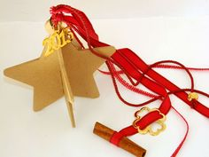3d wooden star decorated with ropes and ribbons and a gold plated ornament along with a cinnamon stick