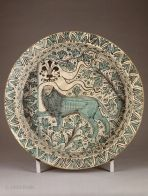 Fifteenth-century majolica bowl from Florence displaying a marzocco/heraldic lion holding the banner of Florence with its lily emblem and featuring more lily stems. (The Louvre)