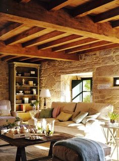 Cottage lounge / living room interior.  Stone walls, wooden beams, shutters, sofa, cushions, throw