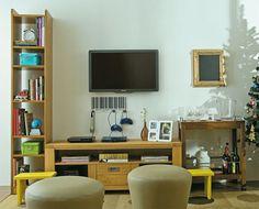 A sala do dia a dia tem TV grande, DVD e videogame e acolhe a todos de modo confortável. Os pufes de couro sintético e os banquinhos de madeira sobressaem no visual neutro do ambiente. Os móveis baixos reforçam a sensação de amplitude. Projeto da arquiteta Thereza Dantas.