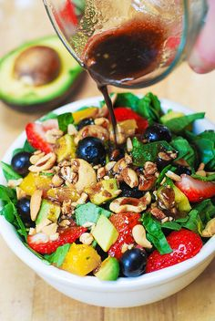 Strawberry spinach salad with blueberries, avocado, mangos and cashews.
