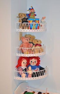 Use Garden Baskets to hold stuffed animals and dolls.  Could use a 3 tier garden shelf and take the baskets off and spray paint them white then mount them in corner. I think they look so pretty and are just adorable for storing dolls and teddy bears above the baby doll furniture :)