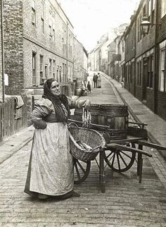 Woman selling fish from a barrel, c. 1910, London