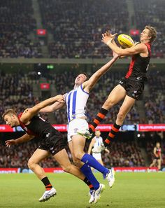 Joe Daniher of the Bombers attempts to mark over the top of Todd Goldstein of the Kangaroos during the round seven AFL match between the Essendon Bombers and the North Melbourne Kangaroos at Etihad Stadium on May 2015 in Melbourne, Australia. Rugby Sport, Sport Man, Essendon Football Club, Fantasy Football Funny, Funny True Stories, Australian Football, Rugby Players, Sports Stars, World Of Sports
