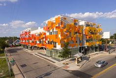 Bercy Chen Studio's East Village takes advantage of the abundance of sunlight in Austin, Texas with a bright red and orange facade that is interspersed with solar photovoltaic panels. Building Costs, Mix Use Building, Green Building, Building Plans, Greenhouse Glass Panels, Dome Greenhouse, Wassily Kandinsky, Villas, Mixed Use Development