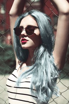 light blue hair. pink lips and old styled shades . plus stripes