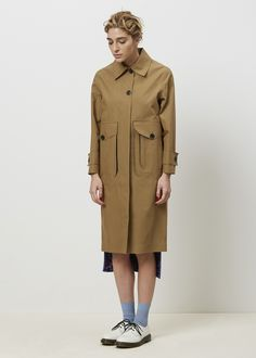 """Mac coat with standard collar in double face bonded cotton tech fabric. Button front closure with half hidden placket, 11"""" inch vent at back. Set in sleeve at front, raglan variation at back. 3D patch pocket variations at front with button closure. Taped interior seams with contrasting black bonded lining. Water resistant. Spot clean only using ironing cloth."""