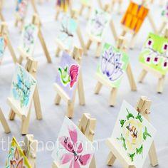 painted mini canvas escort cards set onto mini easels