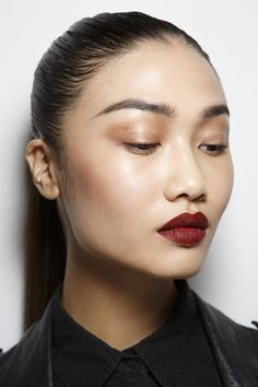 a deep red lip and luminescent lids