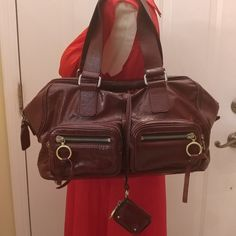 """Authentic CHLOE Leather Betty Satchel in Bordeaux This beautiful like new guaranteed authentic Chloe Betty Satchel in patent grenat/bordeaux color leather is the perfect everyday bag! Holds a Ton!  It features a top zipper closure, a spacious interior, and incredible details such as four exterior zip pockets and a tethered change purse.  A great bag for any stylish fashionista! Retails around $1500.!! ABSOLUTELY STUNNING BAG!!  Large Bag! 9"""" height x 15.5"""" length x 7.5"""" depth & Strap drop…"""