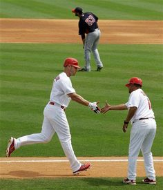 St. Louis Cardinals' Matt Holliday, bottom left, greets third base coach Jose Oquendo as he rounds the bases after hitting a two-run home run off of Minnesota Twins starting pitcher Nick Blackburn (53) in the fourth inning of a spring training baseball game in Jupiter, Fla., Sunday, March 25, 2012. (AP Photo/Patrick Semansky) AP