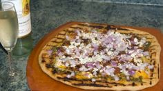 Grilled pesto blue cheese bacon pizza with a glass of Pinot Grigio