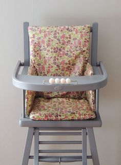 Une chaise haute ancienne repeinte en gris avec un bel habillage en Liberty - An old-style high chair repainted in light grey and covered with a Liberty-print cushion.