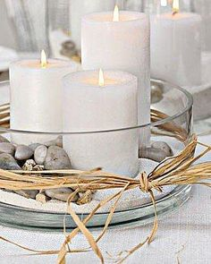 shallow glass vessels with white sand, rocks, shells and pillar candles. Raffia wrap.