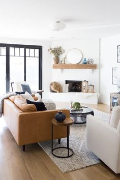 Tulsa Remodel Reveal Modern White Farmhouse with Black Windows and Doors, article sven sofa, modern leather sofa, white brick fireplace wood mantle, raw wood beam mantle, white brick fireplace, West Elm stone tile rug, black and white rugs, black round coffee table, cb2 coffee table, fireplace styling, round gold mirror, round gold mirror above fireplace, how to style a fireplace, spindle chair, Pottery Barn media console, black windows and doors, affordable black windows and doors, Studio…