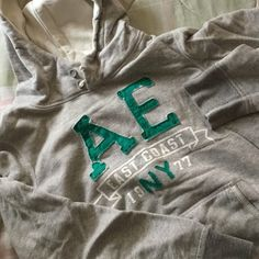 """American Eagle Outfitters Gray Hoodie Simple heathered gray hoodie with distressed teal lettering on front. Instead of drawstrings the hood has 2 buttons. Measures about 25"""" from top of shoulder to bottom. 88% Cotton, 12% Acrylic. Worn 2-3 times. American Eagle Outfitters Tops Sweatshirts & Hoodies"""