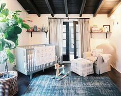 Nursery with a large indoor plant, a simple blue crib, a teal area rug, and a simple armchair