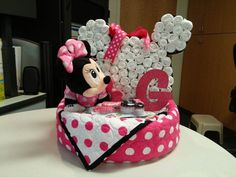 """Minnie Mouse diaper cake 16"""" pizza pan bottom layer/ baby quilt by Ann; 84 size 2, 3 diapers Minnie Mouse/ 88 diapers """"Pamper Swaddler"""" (mostly white) rolled tightly, black and polka dot ribbon Small round layer/ (used to help prop Minnie's head) 13 size 2 diapers Along with misc Minnie mouse items."""