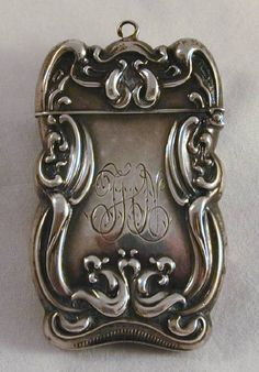 Description: Antique match safe or vesta made of sterling silver. This match safe has a repousse art Nouveau design on both sides. It has a striker on the bottom and a hinged lid with a hoop to attach