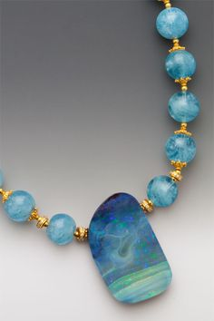 A 156 carat Australian boulder opal - so ripe with stormy seascapes <i>you don't need a weatherman to know which way the wind blows</i> - on beach blue aquamarine rounds with 18K gold accents. ElleSchroeder.com
