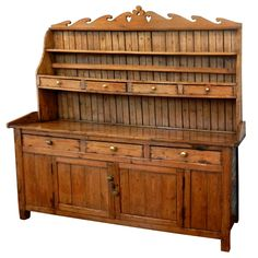 Scottish Pine Dresser (from Red Schoolhouse Antiques at 1st Dibs)  Scotland  circa 1860  An original pine dresser with wave pediment unique to the Scottish Isles.Also cloverleaf and heart detail. Beautifully patinated yellow pine with brass hardware  Price  $2,995