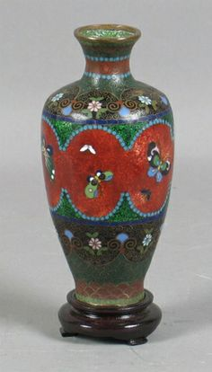 "JAPANESE FOIL CLOISONNE VASE Japanese foil cloisonne vase, wide foil backed band in center with butterfly decoration, top and bottom bands of black, green and iron red with floral and scroll decoration. Comes with wooden stand. Marked: HW. Size: 6""H, 1 1/2""Diam. top, 3""diam. widest part, 1 1/2""Diam. base. Condition: two dings on body, one 1/2""Diam. area of loss along top wide part."