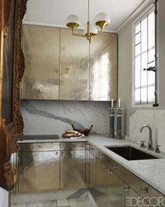 A kitchen designed by Jean Louis Denoit goes glam with hammered brass sheathed cabinetry and polished nickel fittings.