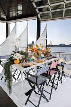 Air plants, rhipsalis, orchids and driftwood accompany this nautical themed table setting.