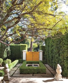The House Pressed Juicery Built - Sculpted hedges and a water feature in the entry courtyard set a formal tone, while stone frog statues from Inner Gardens lend a whimsical touch. A teak gate offers a warm counterpoint to the concrete pavers.