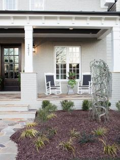 Made+to+withstand+a+range+of+climates,+four+outdoor+rocking+chairs+provide+seating+for+the+home's+welcoming+front+porch.
