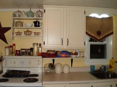 I have very little counter top space so instead of a bread box, I put a shelf under the cupboards to hold not only bread but any other 'things' that usually end up on the counter. I painted the shelf the same as the cupboards. My son found a three shelf knick knack shelf for me, which I installed above the stove to display my tea pots and crockery. Of course I painted it the same color as the cupboards as well. A small kitchen can be functional if you get creative.