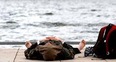 """A break at the lake: North Idaho College student Richard LeMieux, of Hayden, takes a break from classes in Coeur d'Alene on Tuesday. He took advantage of the warm weather and napped at NIC Beach. """"I've got chemistry in 45 minutes,"""" he said. Photo by Kathy Plonka, The Spokesman-Review. #weather #spokane #idaho"""