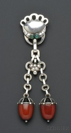 Georg Jensen, early .830 Silver and Amber Brooch, the blossom motif with green onyx cabochon accents, suspending a grape cluster motif, and long drops of circular link chain with amber terminals, lg. 5 in., no. 1, marked 830S, and signed Gi and Georg Jensen.