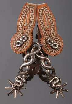 Elegant Mexican Coiled Rattlesnake Spurs with Original Straps Designed with an open heel band to dramatize and accentuate the multiple intertwined snake effect, this regal pair of fully mounted Mexican spurs is constructed using a minimum of eight silver inlaid venomous reptilia forming the heelband, shank, and even the swinging buttons. A lovely but lethal pair of spurs….back away slooowly. Includes original piteado adorned two piece lined leathers. Outstanding condition. 1900 to 1920s.